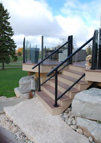 Wood steps with a glass railing are beautiful set into the stone landscape